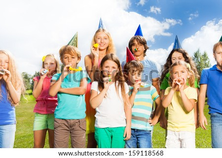 Large group of kids age 5 to 11 outside on a birthday party blowing noisemakers horns and twisted whistles #159118568