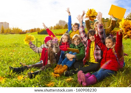 Large group of kids, boys and girls sitting in the grass in autumn clothes with maple leaves bouquets and papers after school with lifted hands after school