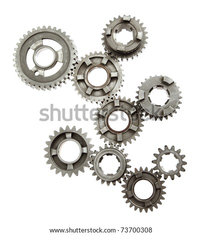 Large group of mechanical gears linked together on white