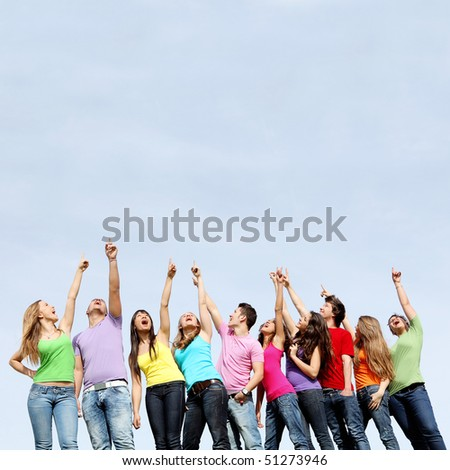 large group of mixed race kids pointing to blank space