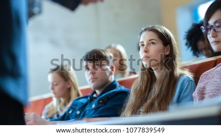 Large Group of Multi Ethnic Students Listening to a Lecture in the Classroom. Bright Young People Study at University. stock photo