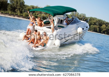 Large group of people sailing and having fun on a yacht.