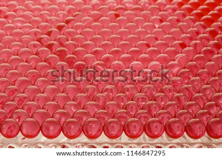 large group of red hydrogel spheres lined on a glass #1146847295