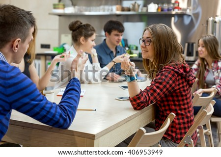 Large Group of Students male and female relaxing at Wood Table of Campus Chat Room talking gesturing having fun