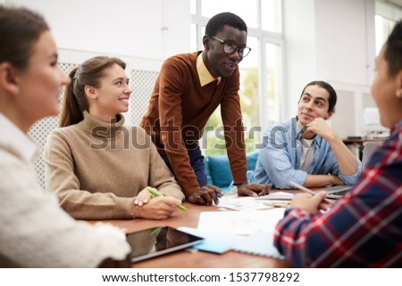 Large group of students working together on team project while studying in college, focus on smiling African-American man heading meeting