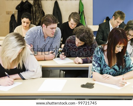 Large group of young adults studying in a classroom