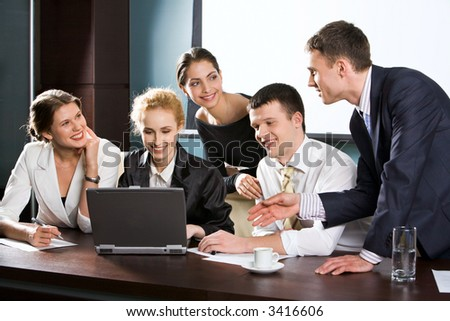 Large group of young businessman gathered together around the laptop discussing interesting question