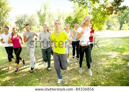 large group of young people running in park