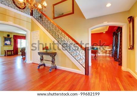 Large hallway and staircase and cherry hardwood floor.