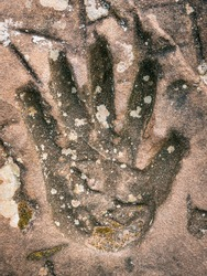 Large handprint into stone. Old weathered print of an adult hand.