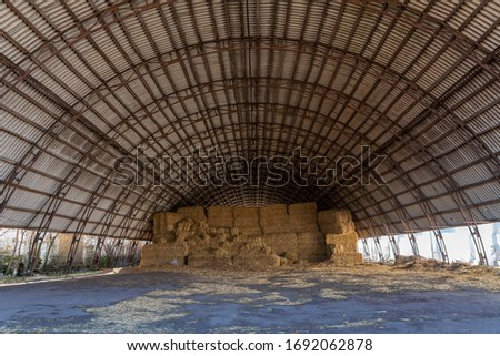 Large hangar for storing straw or hay. Cover for storage. Dry hay in the barn.