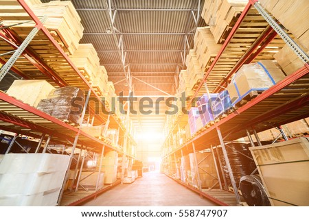 Large hangar warehouse industrial and logistics companies. Warehousing on the floor and called the high shelves. Bright sunlight.