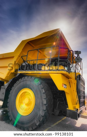 Large haul truck with controled flare and dark blue sky.