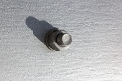 Large head bolt on metal construction as background - engineering concept. Metal head of bolt mounted on a metal surface. Hard shadow from the bolt heads. Close up of bolts holding plates.