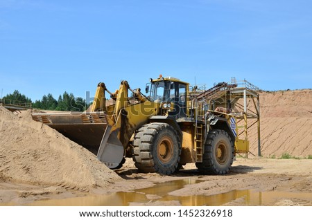 Large heavy front-end loader or all-wheel bulldozer for mechanization of loading, digging and excavation operations in open quarry. Crusher plant with belt conveyor, crushing process, grinding stone