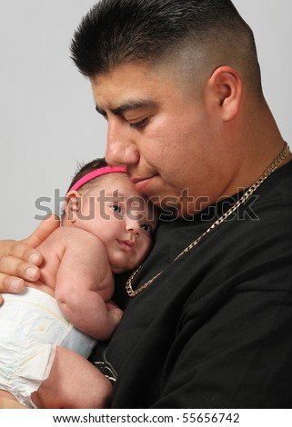 large Hispanic Mexican man holding newborn baby daughter on gray background