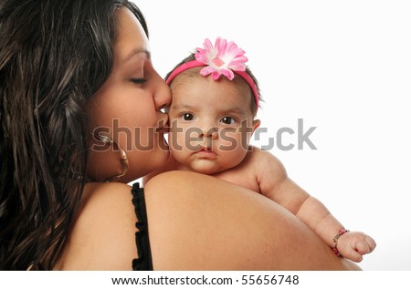 large Hispanic mother holding and kissing cute little newborn baby on the cheek on white background