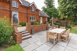 Large historic Victorian house featuring an English garden and patio with wooden furniture. Buckinghamshire, UK
