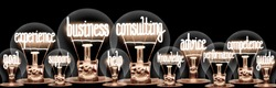 Large horizontal group of light bulbs with shining fibers in a shape of Business Consulting, Help, Support and Experience concept words on isolated on black background.