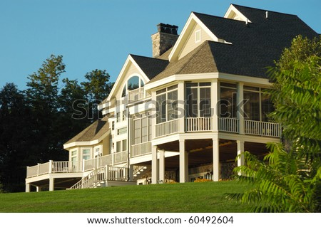 Large House Sitting on top of a Grassy Hill