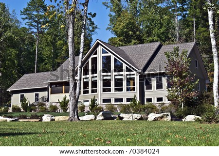 Large house with many windows and rocks in the landscape.