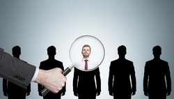 Large human hand with magnifying glass examining man silhouettes against light gray wall. Concept of recruitment. Mockup