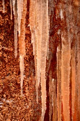 Large icicles close-up, orange cliff in the background. Frozen water, ice texture. Abstract art, natural pattern. Graphic resources, backgrounds, environmental conservation, climate change theme