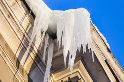 Large icicles hang from a house roof. Dangerous large icicles. Death accident danger in winter.
