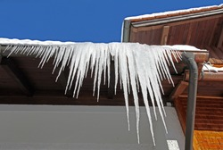 Large icicles hang from a house roof. Dangerous large icicles on a house