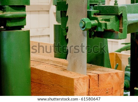 large industrial band-saw cutting a timber into planks for construction