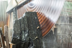 Large industrial cutting machine cuts gray granite stone into slabs. power industrial stonecutter equipment. Huge disc saw for granite or marble cutting in motion. huge saw blade rotates at high speed