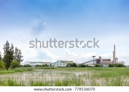Large industrial factory building with conveyor and smokestack at water and green field on blue sky of bright day