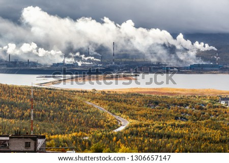 Large industrial metallurgical and chemical plant surrounded by mountains, taiga forest and lakes on a cloudy day. Heavy smoke from smokestacks emit into the air. Monchegorsk, Russia