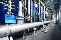 Large industrial water treatment and boiler room. Shiny steel metal pipes and blue pupms and valves.  Industry, technology, special equipment, pure drinking water, biotechnology, chemistry, ecology