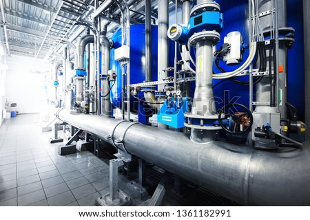 Large industrial water treatment and boiler room. Shiny steel metal pipes and blue pupms and valves. #1361182991