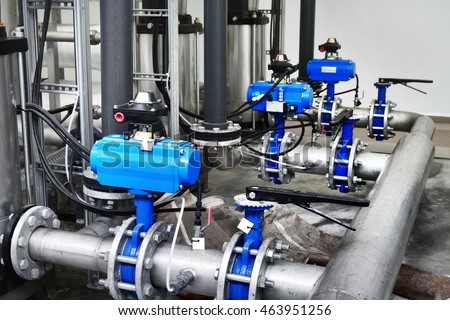 Large industrial water treatment and boiler room. Shiny steel metal pipes and blue pupms and valves. #463951256
