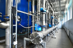Large industrial water treatment and boiler room. Shiny steel metal pipes, blue pumps and valves, close-up. Industry, technology, special equipment, biotechnology, chemistry, ecology, environment