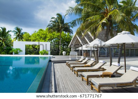 Large infinity pool on the shores of the Indian Ocean with sunbeds and umbrellas in the shade of the palm trees #671771767