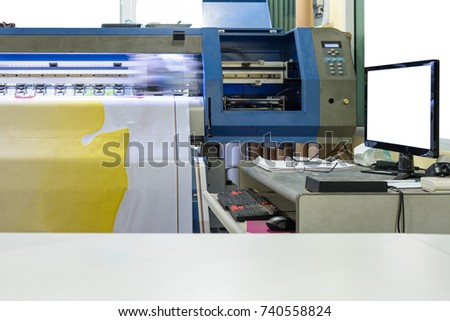 Large Inkjet printer working on vinyl banner with computer control - Shutterstock ID 740558824