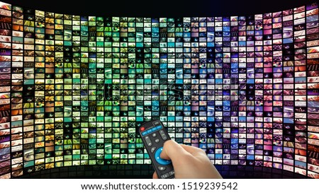 Large interactive TV with many smart channels, man's hand with remote control.