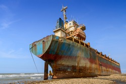 Large iron cargo ship run aground at sea bay. Industrial sea vessel shipwreck on coastline after storm accident.
