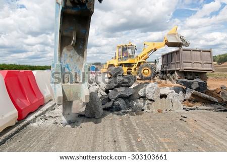 Large jackhammer breaking street asphalt paving during road construction works and wheel loader loading crushing asphalt pieces into dump truck