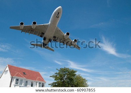 large jet aircraft on  landing approach over suburban housing