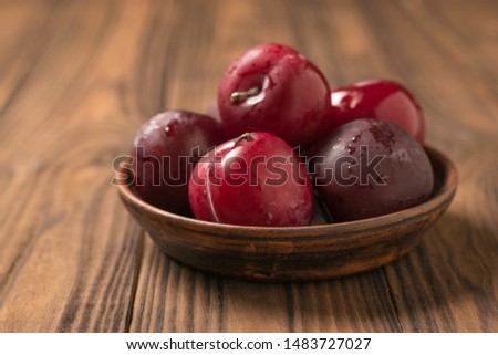 Large large ripe plums in a clay Cup on a wooden table. Fresh fruit harvest. #1483727027