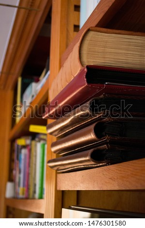 Large leather covered picture albums stacked on one another on a shelf, with more books in the background.