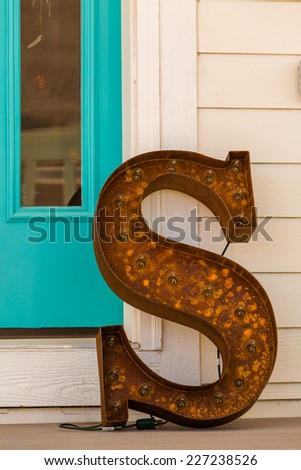 Large letter S made from rusted metal on the front poarch.