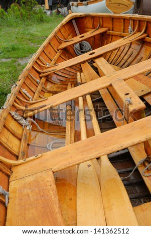 Large life boat or row boat with newly finished wood interior sitting out in the rain