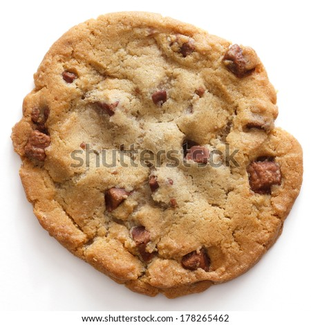 Large light chocolate chip cookie on a white surface shot from above