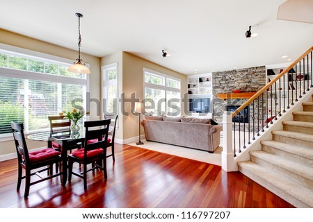Large living and dining room with staircase, cherry hardwood.