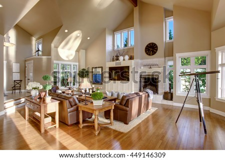 Large living room interior design with high vaulted ceiling and leather sofa set. Has telescope by the window